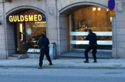 Polisen närmar sig guldsmedsbutiken med dragna vapen.