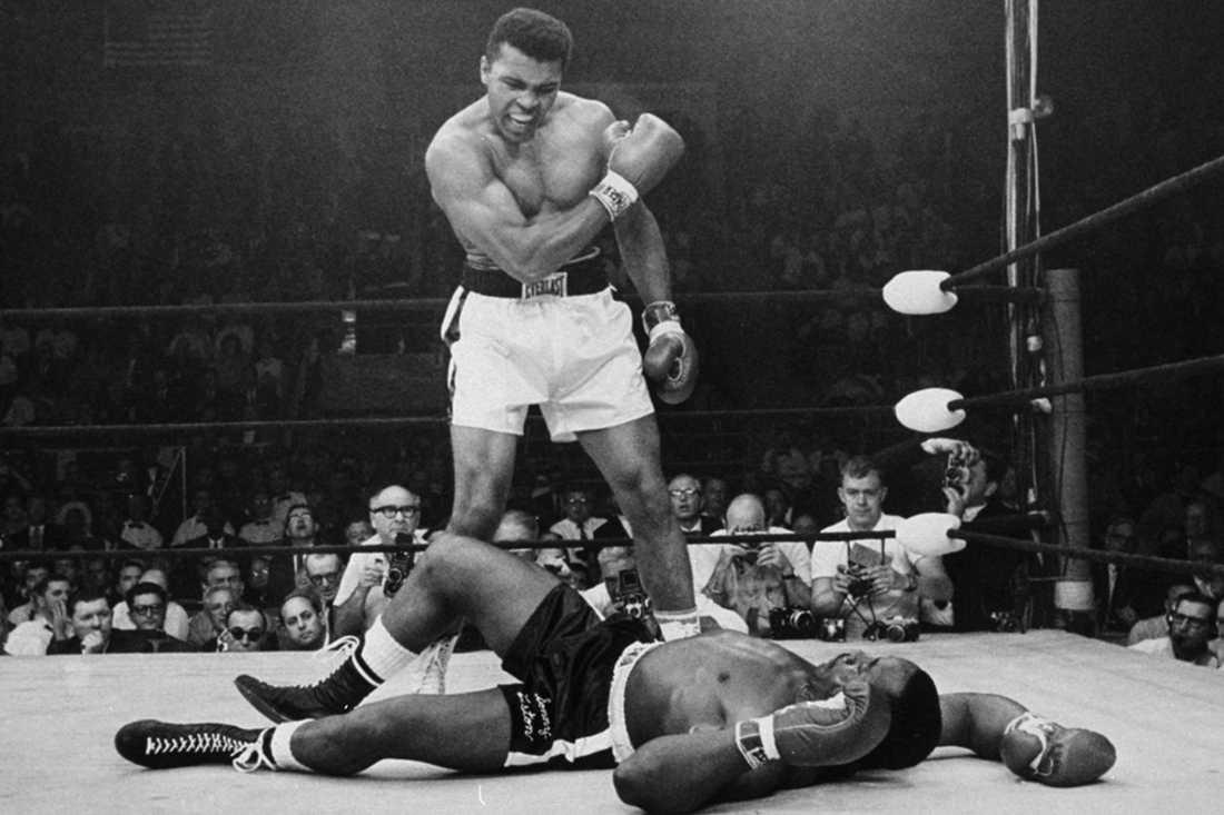 """Muhammad Ali (1942-) vrålar och gestikulerar efter sin berömda """"Phantom Punch"""" på Sonny Liston (1932-1970) i deras returmatch om titeln i Lewiston, Maine 25 maj 1965. Trefaldige tungviktsmästaren Ali rankas av många som den bäste någonsin."""