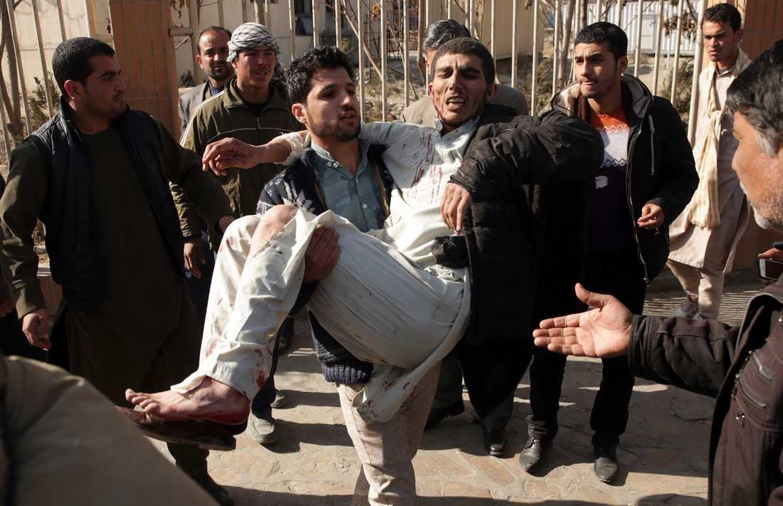En skadad man får hjälp efter en självmordsattack i Kabul i januari. Arkivbild.