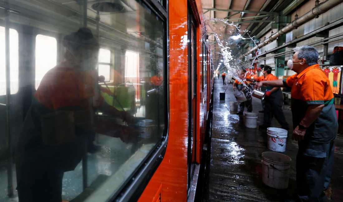 Renhållningsarbetare tvättar en tunnelbanevagn i Mexico City i syfte att motverka spridningen av det nya coronaviruset.