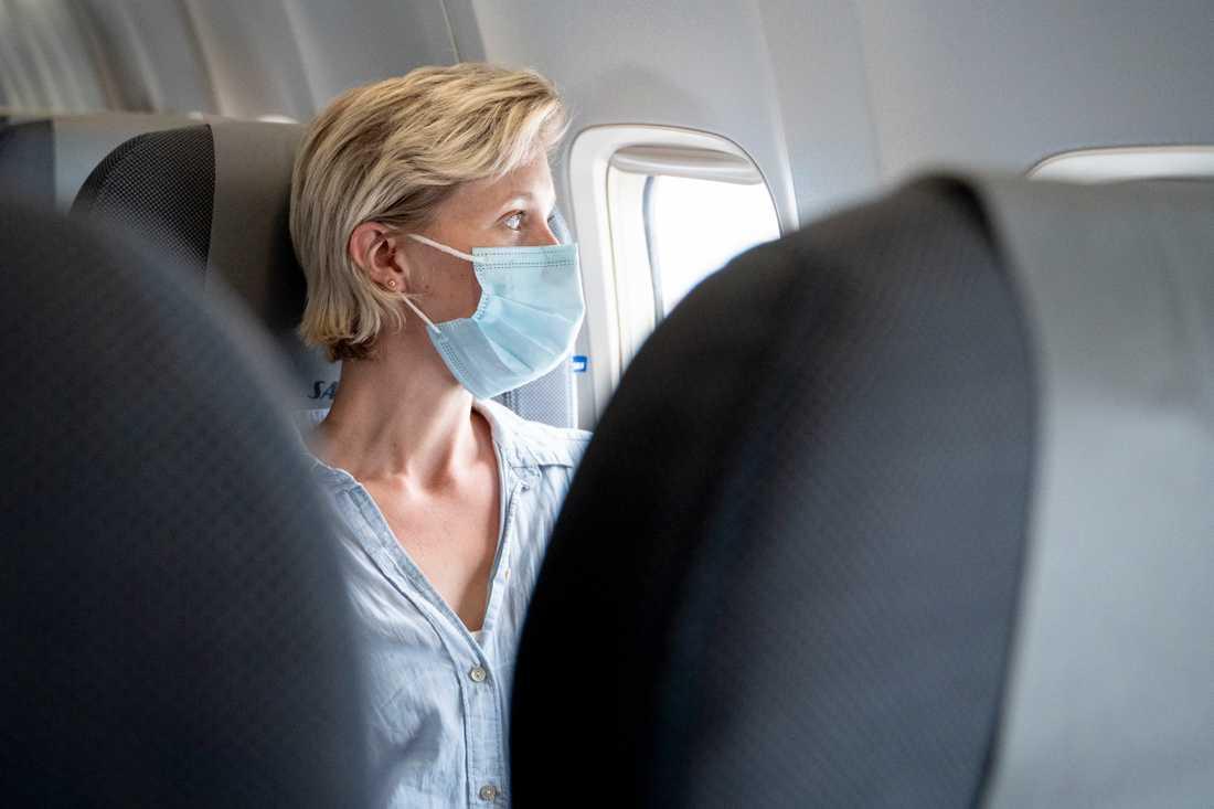 Kvinna med munskydd på flygplan. Arkivbild.