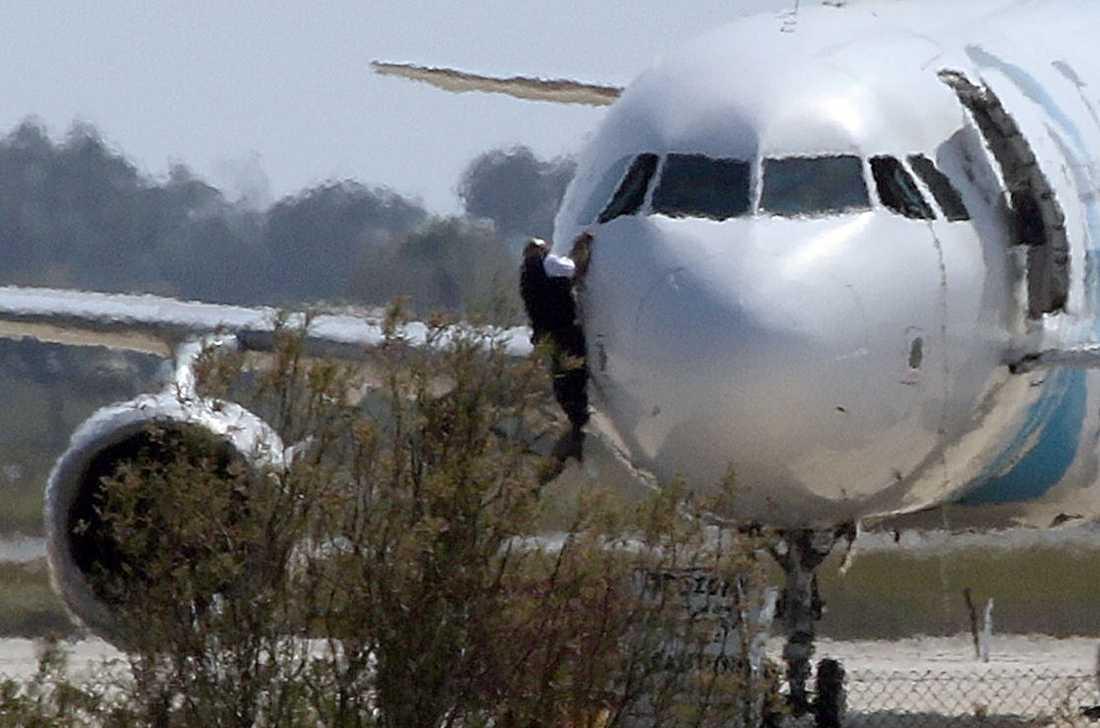 Här flyr en av personerna som hållits som gisslan ut genom fönstret i cockpit.