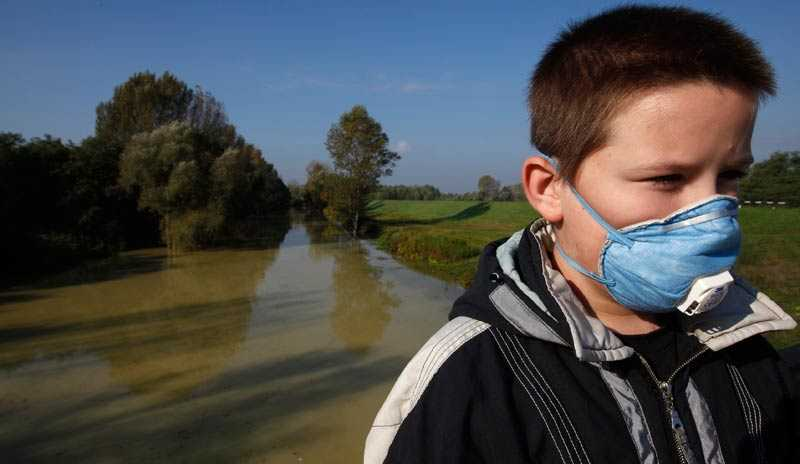 Efter utsläppet En pojke försedd med munskydd bredvid floden Marcal.