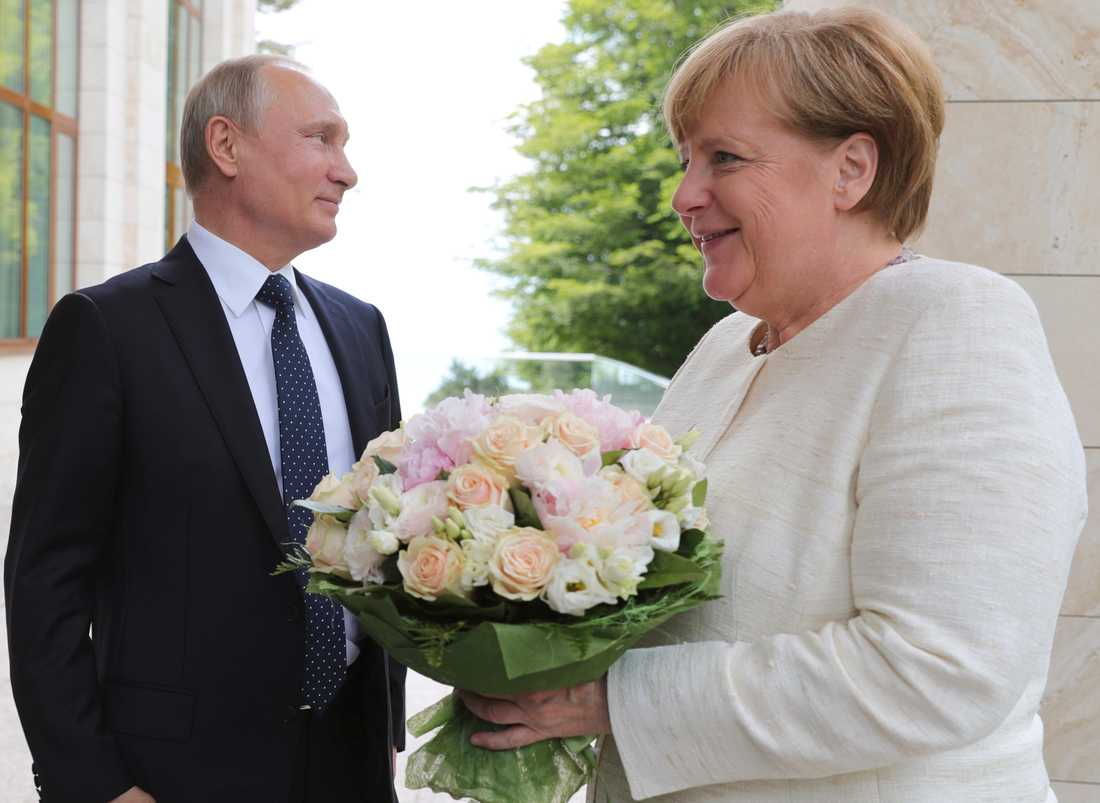 Rysslands president Vladimir Putin hälsade Tysklands förbundskansler Angela Merkel med en bukett blommor när hon besökte ryska semesterorten Sotji i maj. Arkivbild.