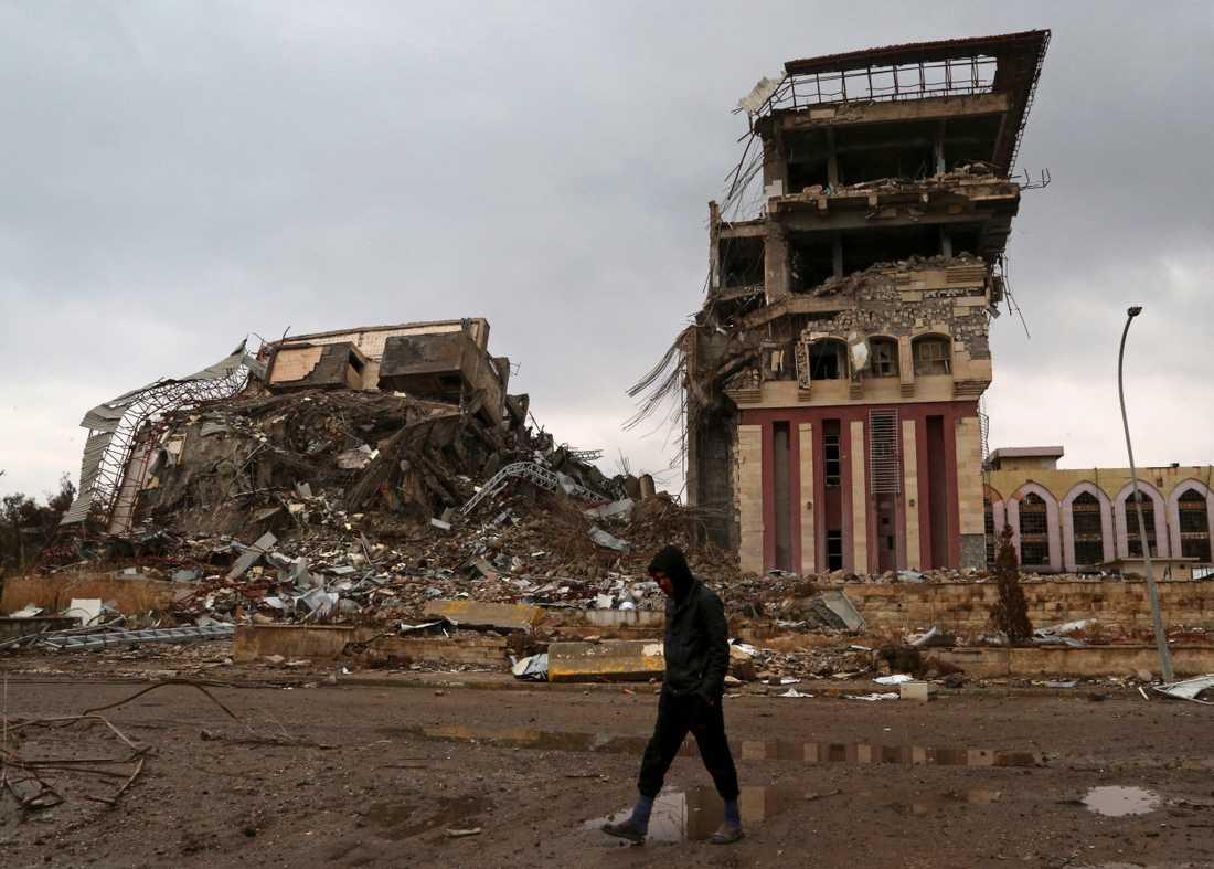 En student framför universitetet i den irakiska staden Mosul, vars byggnader förstördes i striderna om staden.