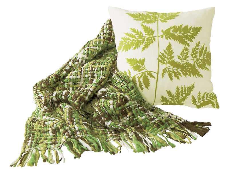 Piffa den vita soffan med en grönmönstrad pläd, 99 kr, vit kudde med grön växt på, 69 kr, från Jotex.