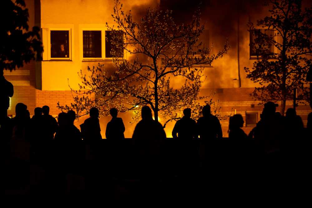 NICLAS HAMMARSTRÖM I fönstret står ett par och ser sina grannars bilar brinna upp. Mitt emot står ungdomarna som orsakat branden.