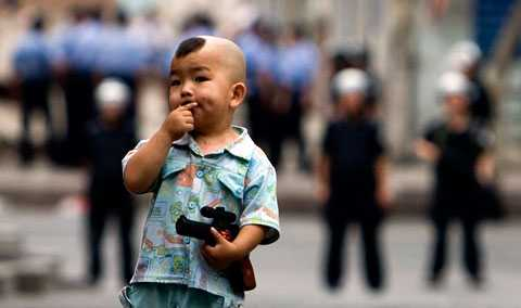 En uigurisk pojke med ett leksaksvapen i en allé där kravallpoliserna syns i bakgrunden efter en mindre protest som följde på fredagsbönen i Ürümqi.