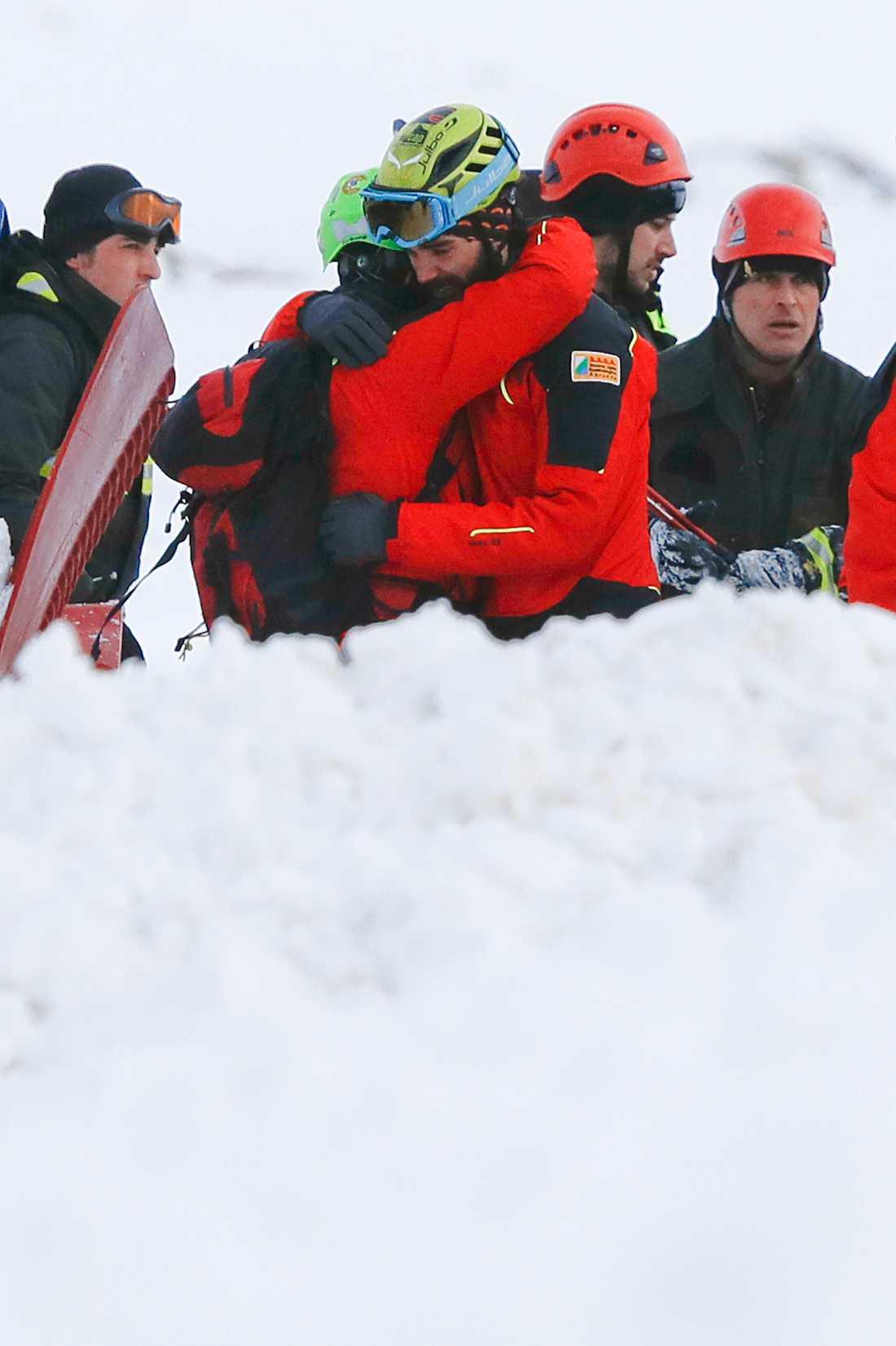 Räddningspersonla atröstar varandra vid nedslagsplatsen.