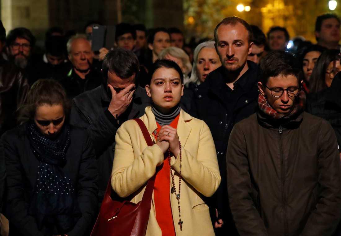 En betraktare knäpper händerna framför Notre-Dame i Paris.