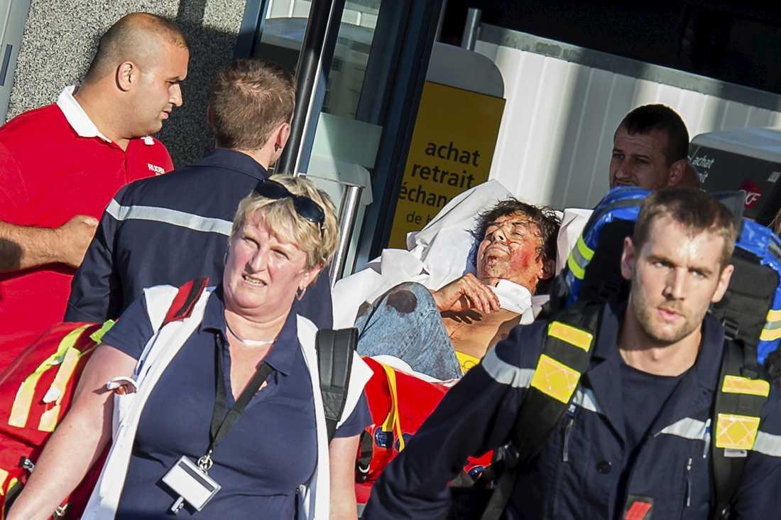 En skadad passagerare bärs bort på bår.