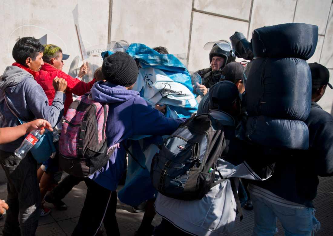 Migranter pressar på mot polisen vid gränsövergången i Tijuana i Mexiko.
