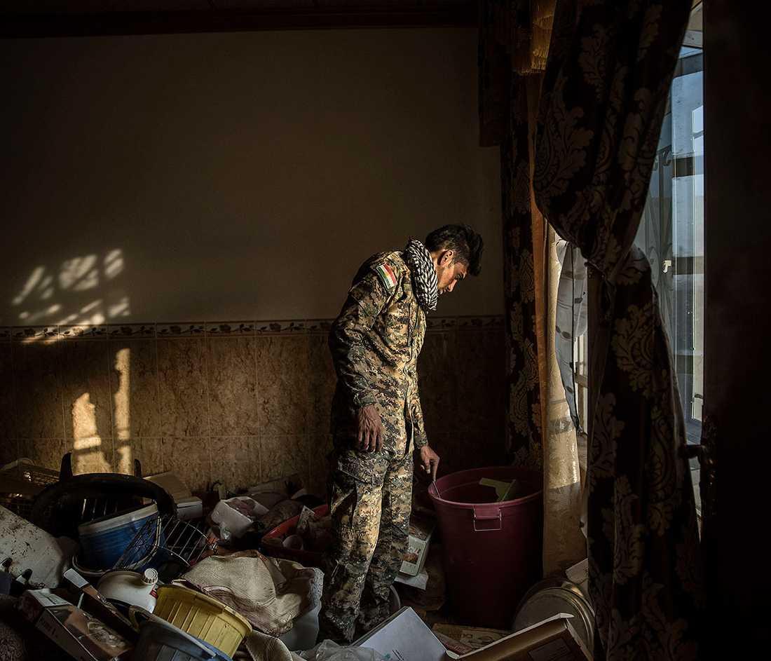 En kurdisk soldat går igenom sakerna i ett hus som nyss återtagits från IS.