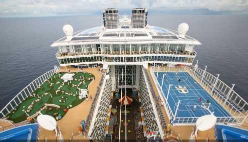 Oasis of the seas: Tennisplan och golfbana på övre däck I avgrunden mellan syns balkongerna till några av de 2700 hytterna. I bakgrunden Karibiens blå himmel och vatten.