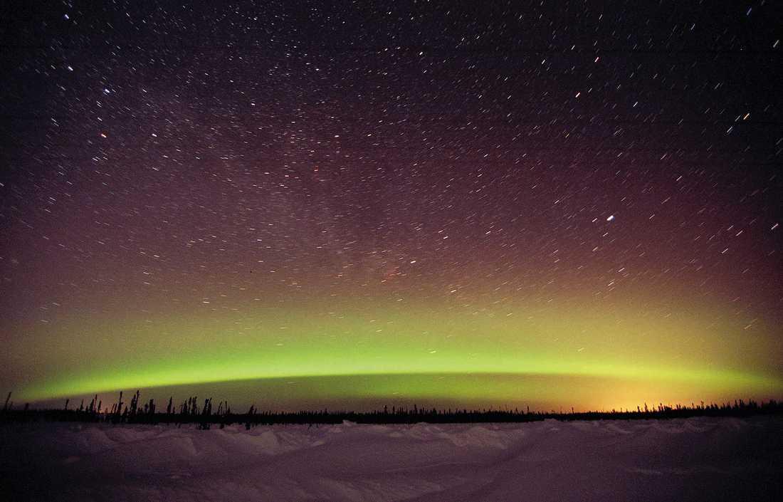 Grönt norrsken på stjärnhimmel. Okänd fotoplats.