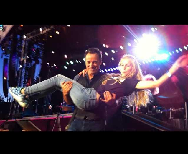 Bruce håller upp henne på scenen.