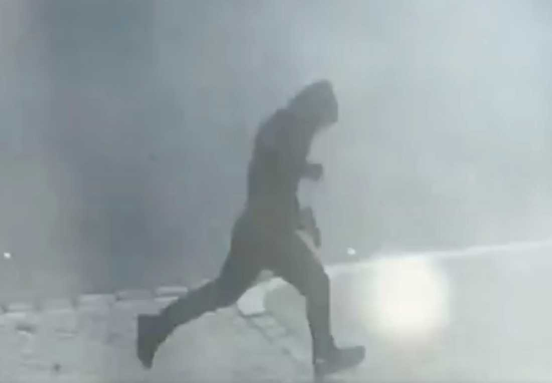På bilder från en vittnesfilm syns skytten springa med draget vapen.