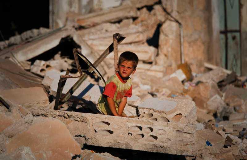 INGRIP – VIA FN En syrisk pojke sitter i ruinerna efter ett hus som förstördes i ett anfall mot staden Taftanaz av den syriska armén tidigare i år. Nu kräver svenska FN-förbundet att en internationell styrka sänds till gränsen mot Syrien. Foto