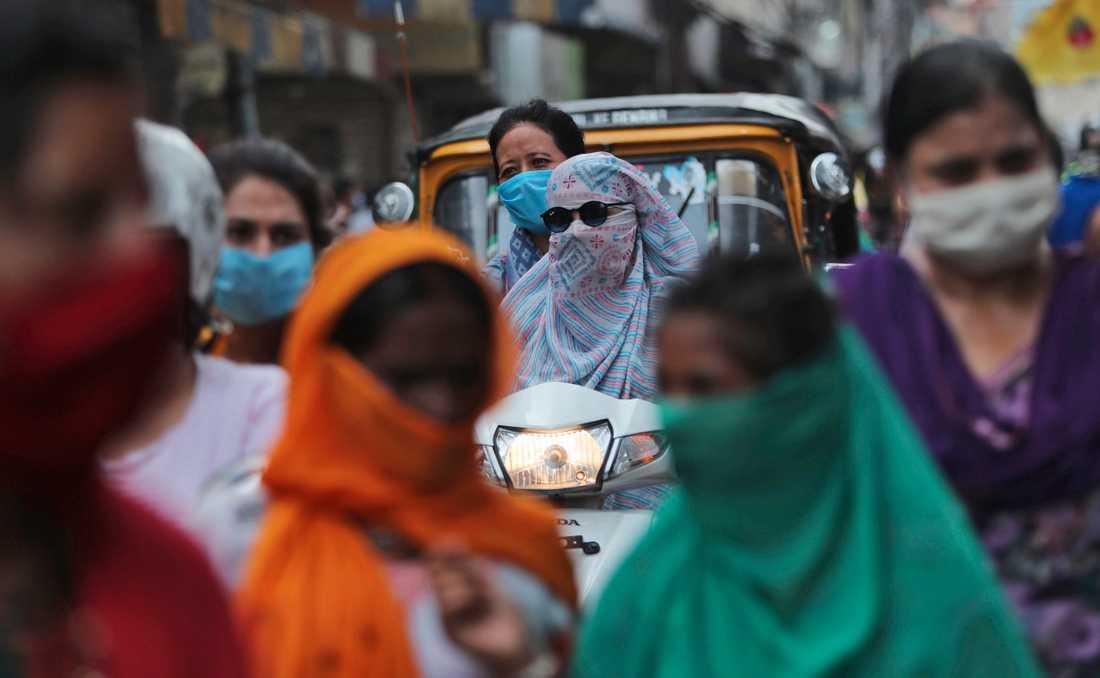 Människor med munskydd vid en marknad i indiska Jammu. Indien har blivit ett av de värst drabbade länderna i världen.
