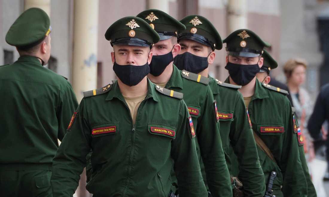Soldater med ansiktsmasker marscherar i ryska S:t Petersburg. Landets dödstal är lågt i förhållande till antalet smittade.