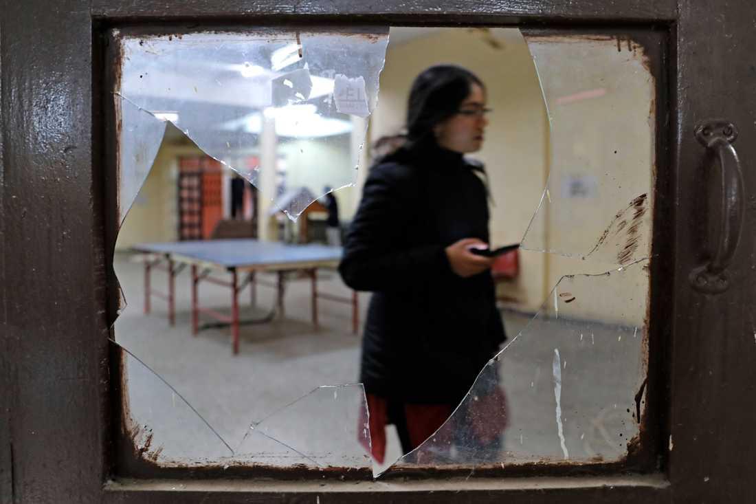En student går genom en vandaliserad matsal på universitetets campus.