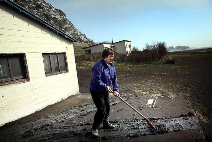 Diana Augustsdottir skottar bort aska från ingången till sin ladugård.