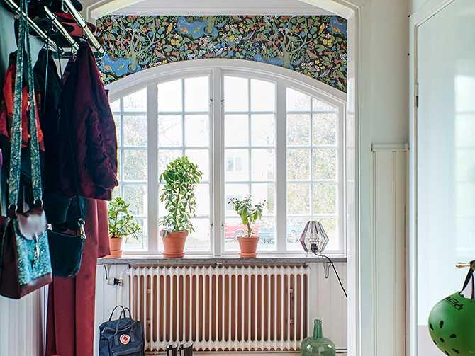 """I hallen möts man av den färgglada tapeten """"Paradiset"""" av Josef Frank och vackra spröjsade fönster skapar ett extra varmt välkomnande."""