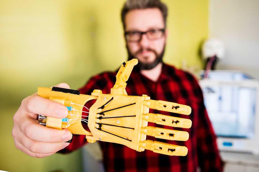 God dag. Lars Hansson, 50, med en handprotes som han tillverkat i plast med sin 3D-skrivare utifrån en mall. Protesen är mekanisk och tar en natt att skriva ut på skrivaren.