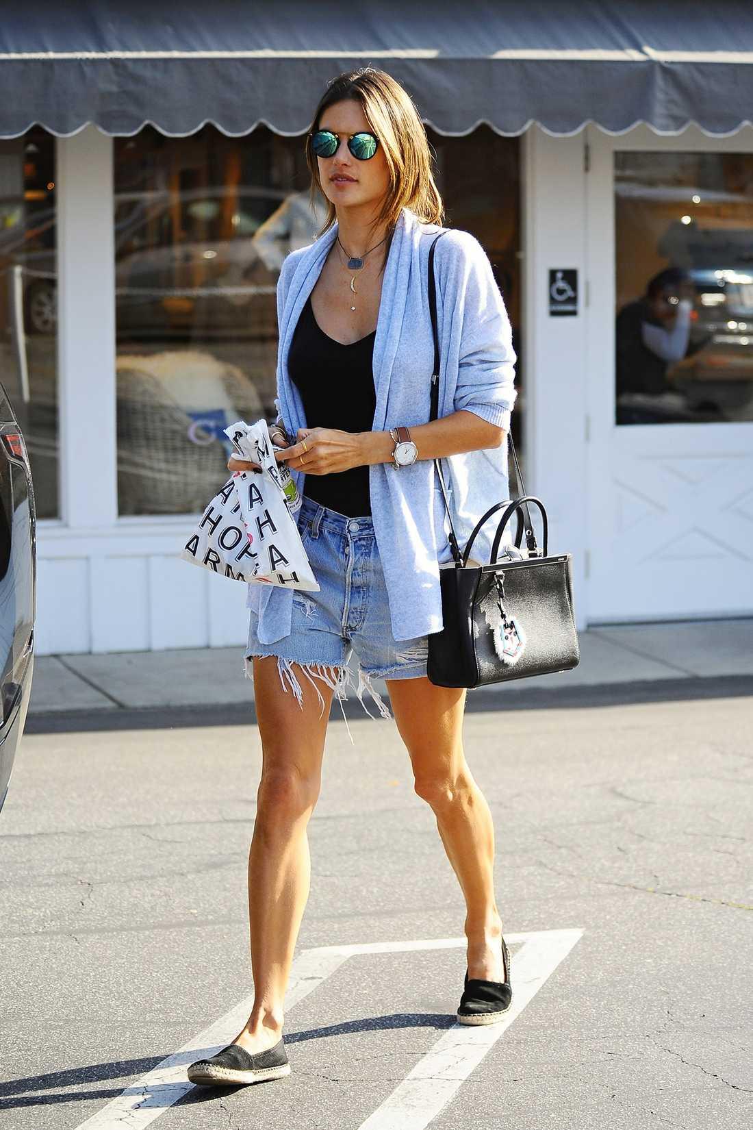 Alessandra Ambrosio Bohochica Alessandra i avklippta jeansshorts som hon stylar med en stor kofta och bekväma skor.