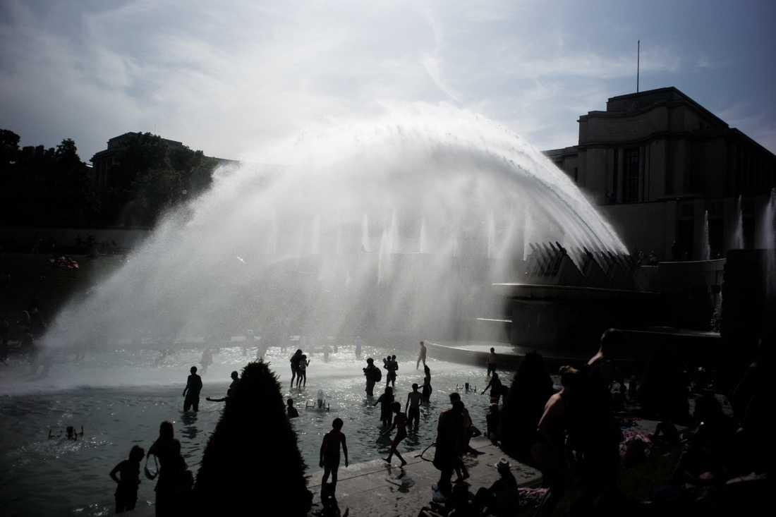 Människor svalkar sig i fontänen i Trocaderoträdgården i Paris den 28 juni, då värmen senast slog till i huvudstaden.