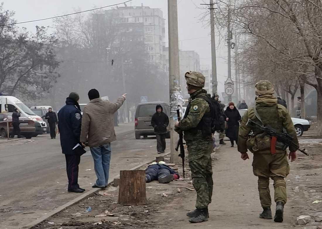 Ukrainska regeringssoldater patrullerar i Mariupol. På gatan ligger en död man.