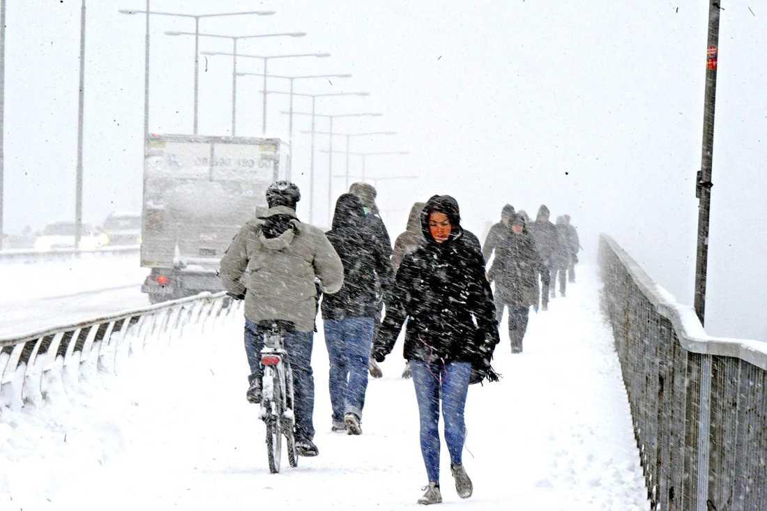 Här kämpar folk mot snö och kyla på Västerbron i Stockholm.