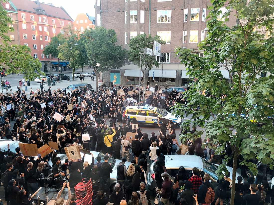 En kvinnlig polis knäböjer bland demonstranterna i Stockholm.
