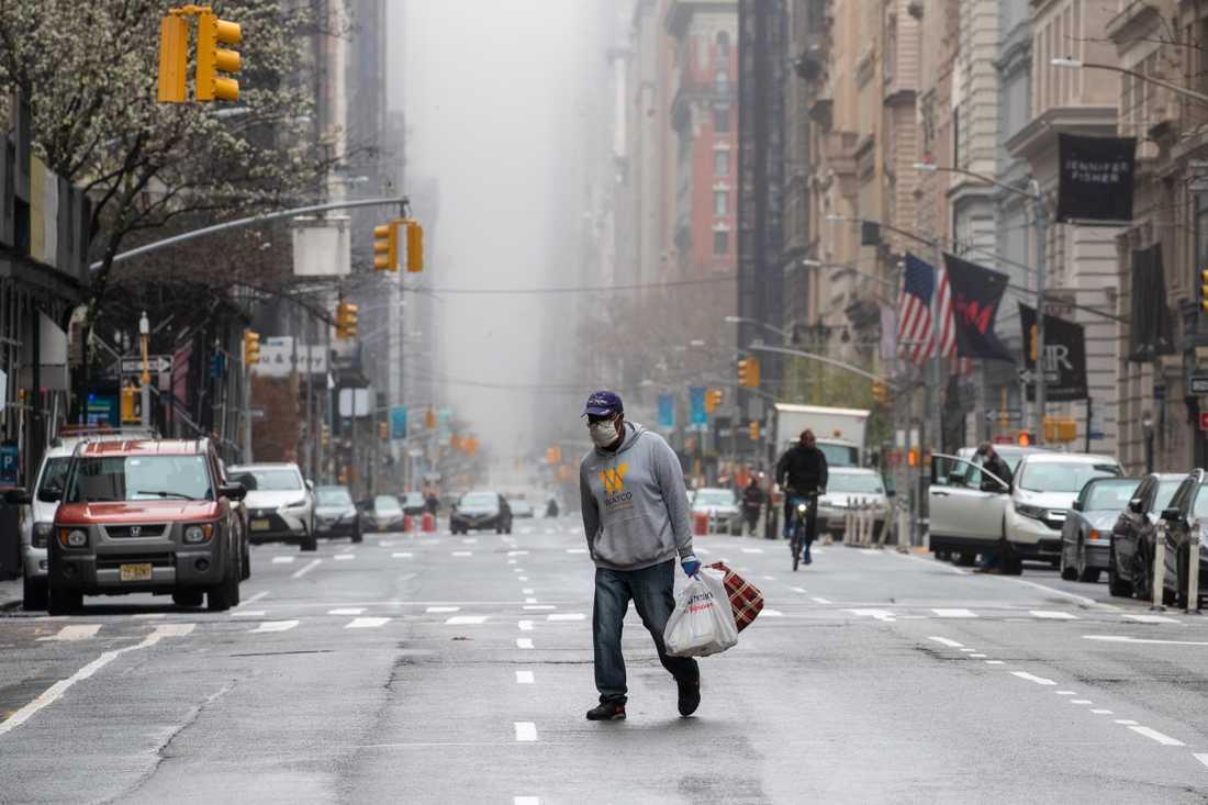 En man med munskydd korsar femte avenyn i New York.