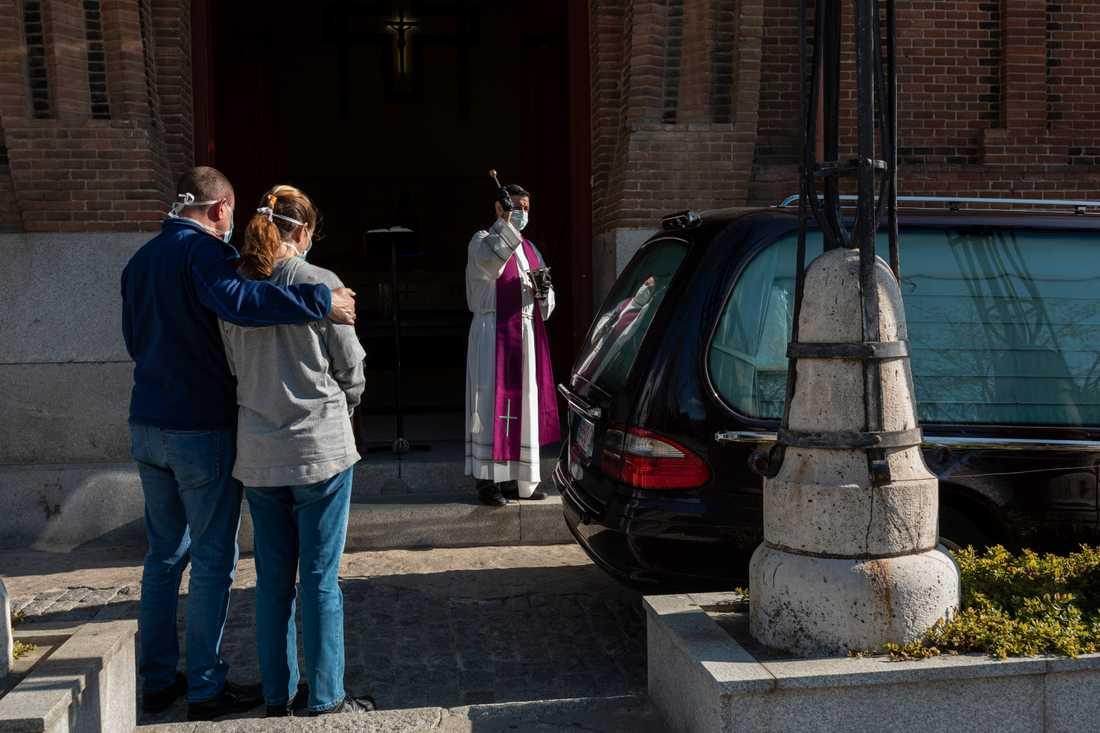 En präst genomför en begravningsceremoni på en av Madrids kyrkogårdar.