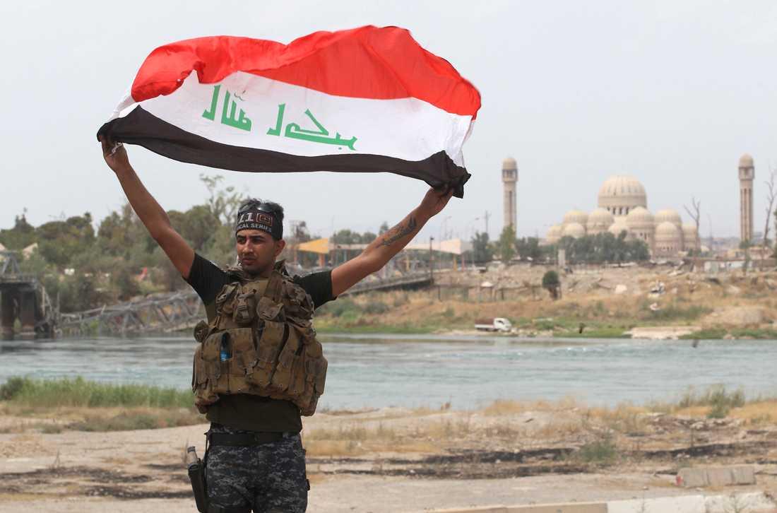 Irakisk federal polis höjer en flagga i Gamla stan i Mosul.
