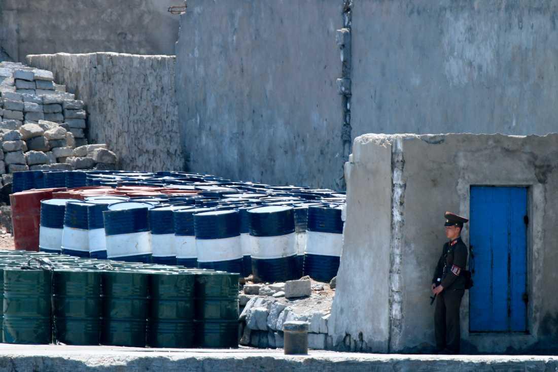 En nordkoreansk soldat vaktar oljetunnor i staden Sinuiju nära gränsen mot Kina. Arkivbild.