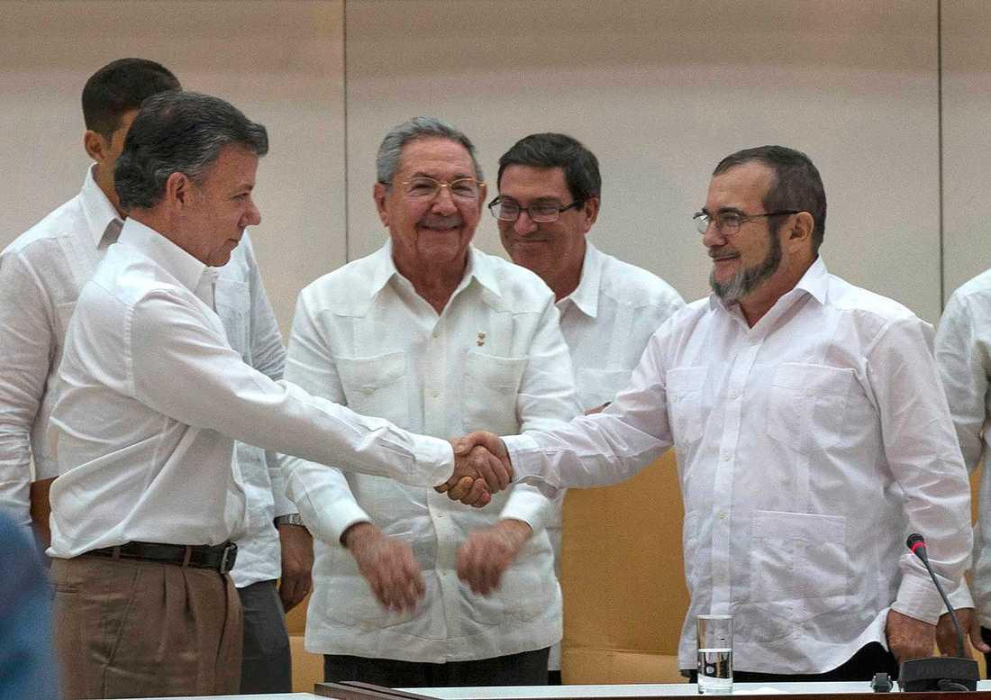 Juan Manuel Santos skakar hand med ledaren för Farc, Rodrigo Londono. Bakom står Kubas president  Raúl Castro, som hjälpte till att medla i fredsförhandlingarna.