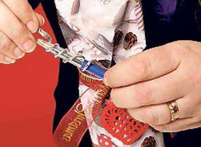 """5. Klipp """"ormtungor"""" i ändarna. Vira ståltråd runt bandet, forma ändarna runt en penna så att de blir skruvade. Häng på hjärtat. Klart!"""