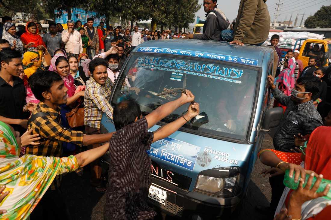 Protesterande textilarbetare i Bangladesh vandaliserar en bil i förorten Savar i Dhaka.