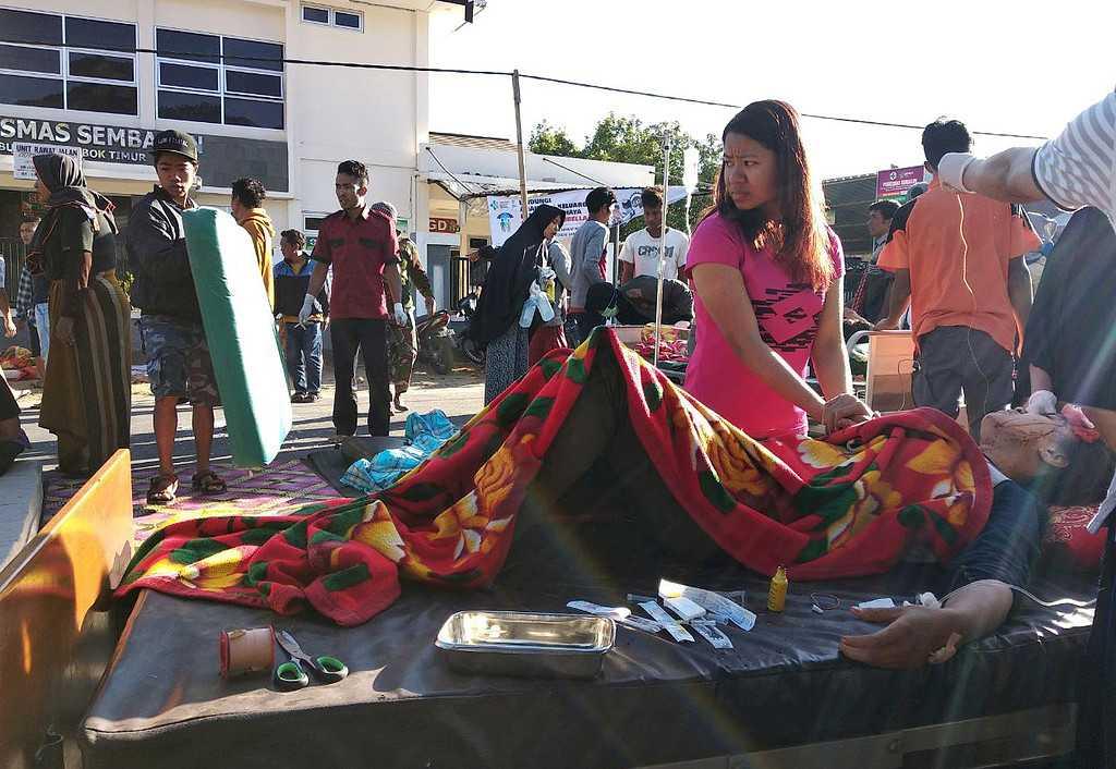 En kvinna står intill en skadad person utanför ett sjukhus på Lombok.