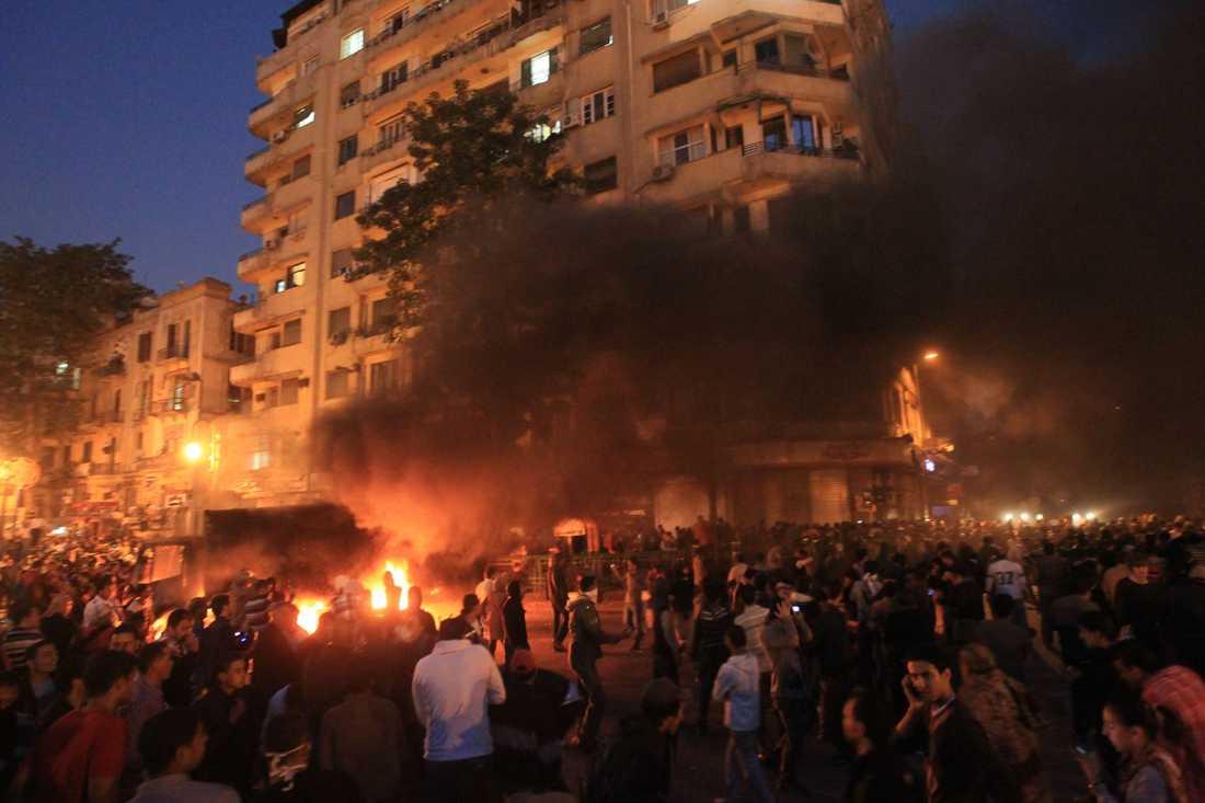 En uppretad folkmassa har tänt eld på ett polisfordon på Tahirtorget i Kairo.