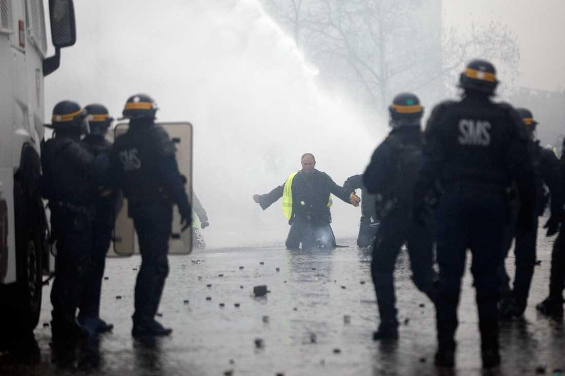 Polisen har satt in vattenkanoner mot demonstranterna i Paris. Ett 60-tal personer har gripit.