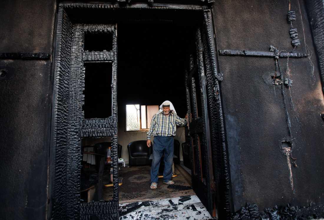 En man tittar på huset som brändes ned i attacken i juli 2015. Arkivbild.