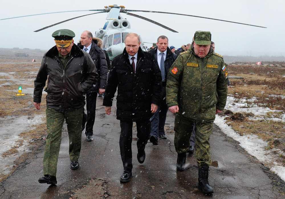 Vladimir Putin, i mitten, flankerad av försvarsministern Sergei Shoigu (till vänster) och toppmilitären Anatoly Sidorov under en militärövning i St.Petersburg.