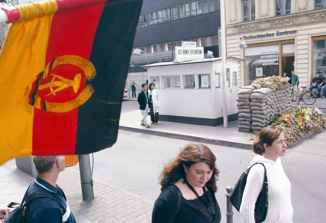 En östtysk flagga vajar vid den tidigare gränsövergången Checkpoint Charlie i Berlin, numera ett turistmål.