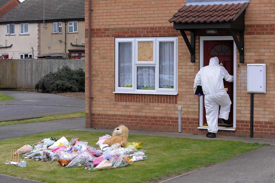 En tekniker går in i huset där mamma och dottern mördades. På gräsmattan och sörjande lagt blommor.