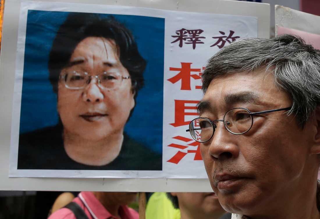 Gui Minhais porträtt flankerar Lee Wan Kee, en av bokhandlarna som fängslades tillsammans med Minhai första gången, 2016.