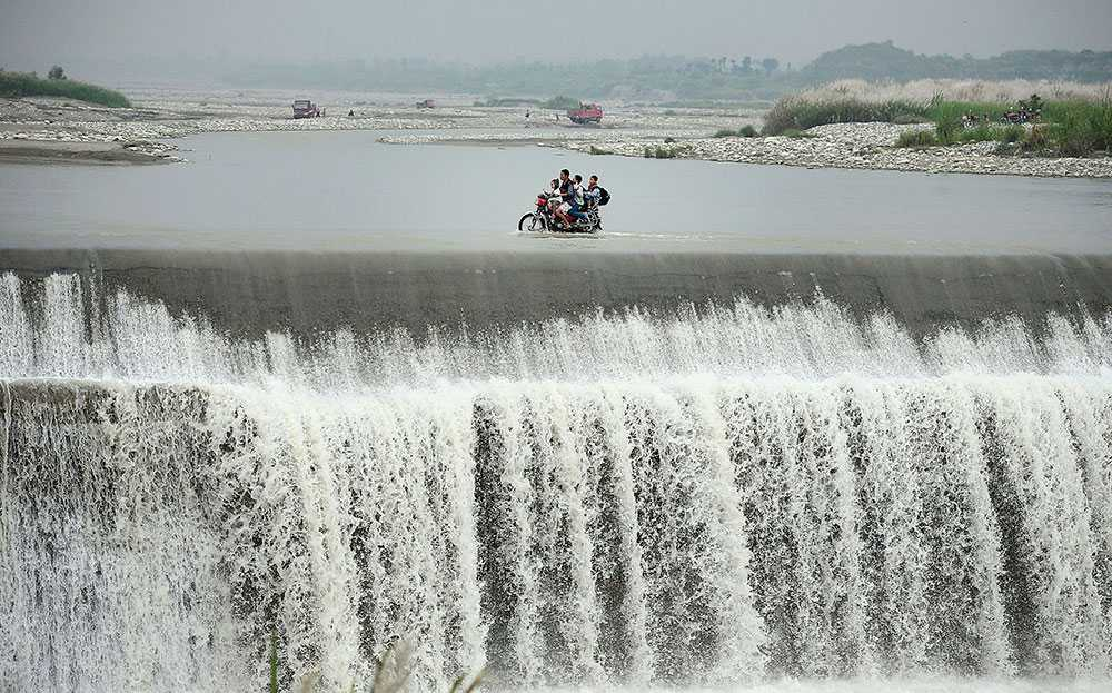 En man skjutsar sina barn på en motorcykel farligt nära ett vattenfall i en översvämmad damm i den kinesiska provinsen Sichuan.
