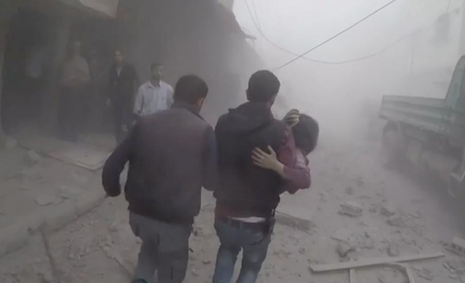 Två män bär en skadad i Douma i östra Ghouta.